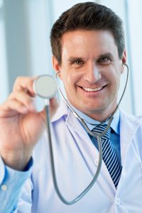 smiling male doctor in a lab coat holding a stethoscope up to the camera