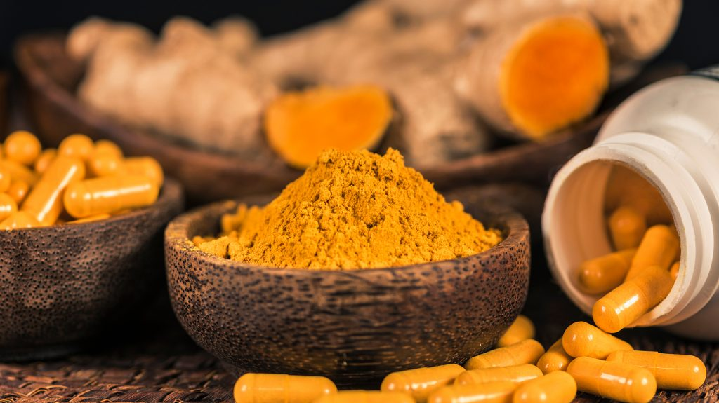 several-bowls-of-turmeric. One-bowl-of-fresh-turmeric-root-a-bowl-of-ground-up-turmeric-powder-and-a-bowl-of-turmeric-in-capisule-form. Bottle-of-turmeric-capsules-spilled-in-front-of-the-bowls