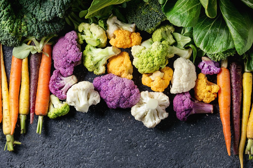 An array of colorful carrots, broccoli, purple broccoli, cauliflower, and lettuce on a black background