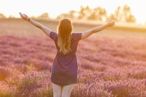 A young woman arms stretched out in the fading sun in a lavendar field