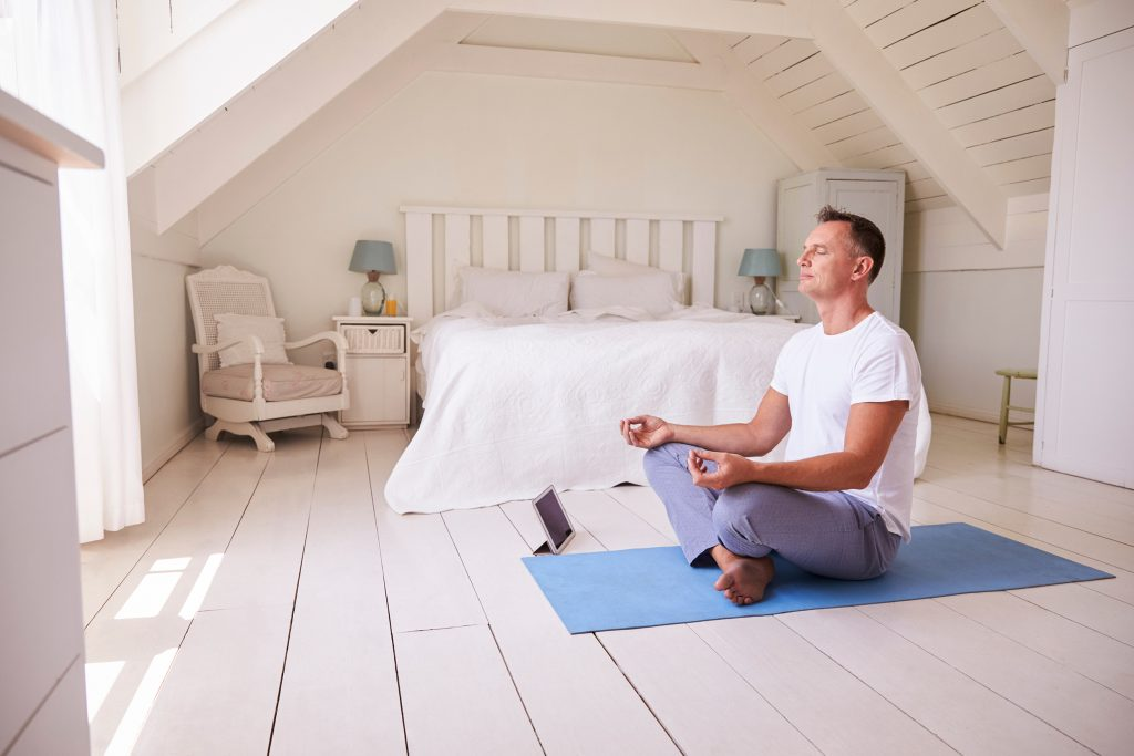 Middle aged man in an all white bedroom meditatiing peacefully facing the window on a blue yoga matt.