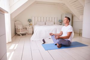 relaxed man sitting legs crossed on a blue yoga mat in his room meditating