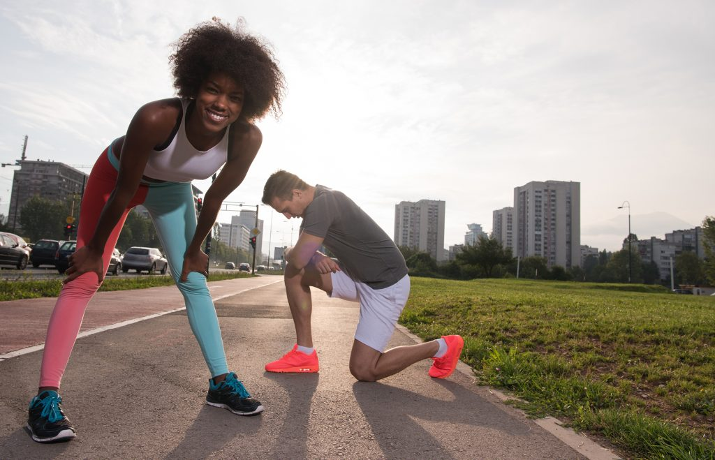 Young woman in running gear bending down smiing into the camera as her male partner is kneeing on the asphalt resting. City landsape in teh background
