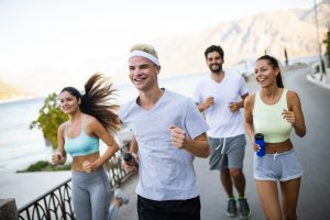 four young adults wearing workout clothes  smiling and jogging on a bike path