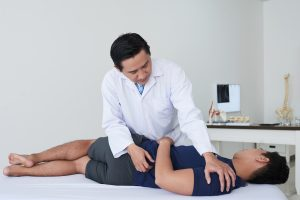 male chiropractor is working on a female patient who is laying on a table in his office