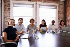 Group of happy smiling coworkers sitting around a large table with computers out  in a large meeting room