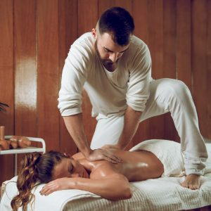 Woman laying on a massage table enjoying a deep tissue massage from a male masseuse  One of the many holistic procedures covered by Nova Path FInder