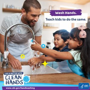Young father helping his small  son and daughter to wash their hands properly over the sink.