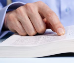 a man;'s finger pointing to text in a book.