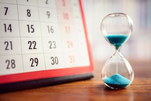 A calendar and a hour glass representing open enrollment for our insurance 365 days a year