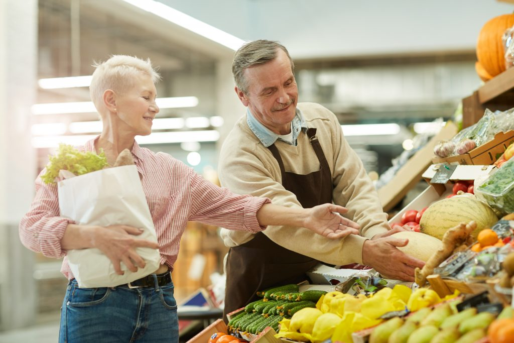 An elder male grocer helping a older fit woman who is holding a bag full of groceries to a watermelon that is on display with other fruits and vegetables