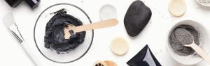 Two-bowls-of-activated-charcoal-stirred-up-next-to-makeup-brushes