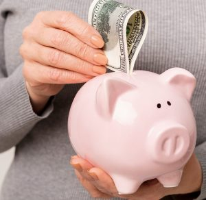 woman wearing a grey sweater putting a hundred dollar bill in a pink piggy bank