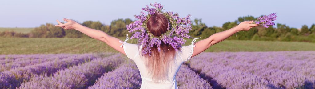 young woman dressed in white wearing a crown of lavander plants arms stretched in front of a lavander field