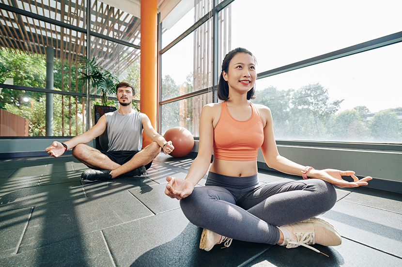 young lady and gentleman in work out clothes sitting crossed legged on a yoga mat in a yoga studio meditating in the sunlight