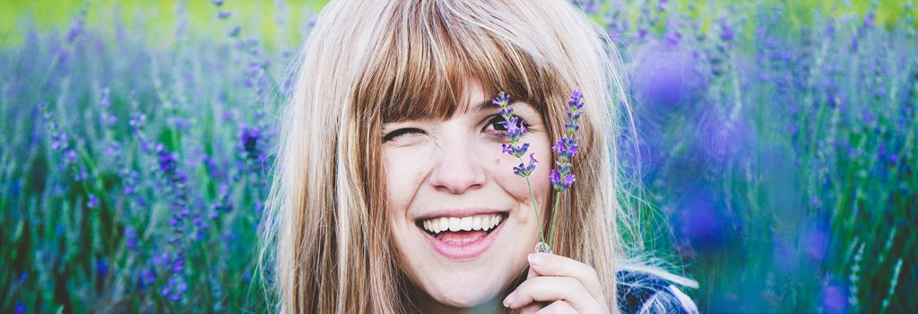 Young woman in a lavader field smiling as she holds up s lavander stalk to her eye.