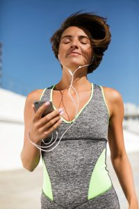 Young woman in grey work out clothes smiling with hey eyes closed and heaphones in listening to music.