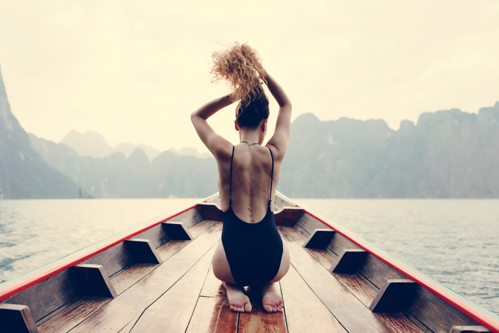 young fit woman in a black backless bathing suit putting her hair in a ponytail whole kneeling on the bow of a boat that is in the ocean with mountains in the background