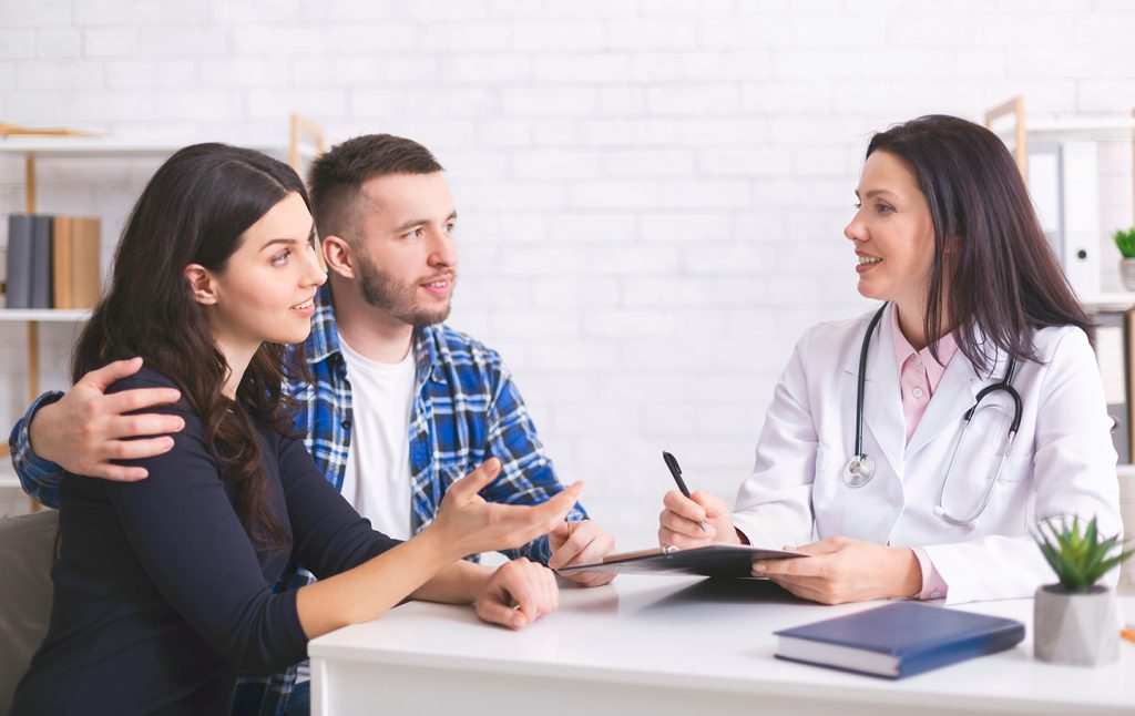 young couple sitting at a desk  in a doctor's office discussing options with the female doctor who is taking notes on a clipboard.