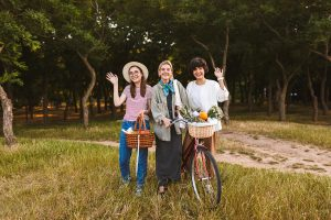 three woman standing next to a groove of trees. The young woman on the left is holding a basket a ful of fruits and vegetables waving to the camera. The woman in the middle has a bike with a basket also filled with fruits and veggies. The womamn on the right is smiling and waving to the camera