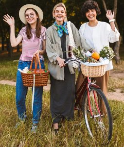 three women smiling at the camera The woman in the middle  is holding a bike with  a basket full  of flowers and fruit. The youngest woman is holding a basket as she waves to the camera. On the far right is a woman in all white waving as well to the camera