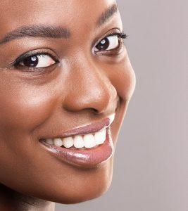 A woman's head shot smiling perfect white teeth into the camera