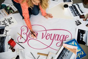 young woman in a pink sweater and blue jeans  working on a large pink BON VOYAGE sign surrounded by pictures, books, and other signs