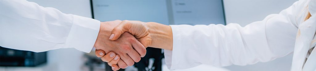 doctor in white lab coat and a male in a long white button down shirt shaking hands in agreement