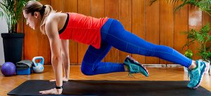 athletic young woman in red and blue workout clothes doing mountain climbers on a black yoga mat