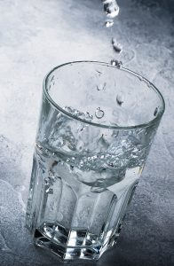 half full cup of water with large drops of water falling into the cup