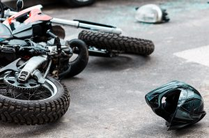motorcycle crashed on the asphalt with a helmet lying next to it