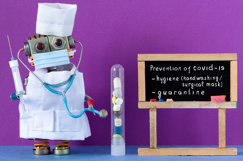"""little robot wearing a surgical mask, smock, and hait holding a needle and stetloscope. Standing nect to a blackboard made of popsicle sticks that have """"prevention of Covid-19; hygene (handwashing/surgical mask and quarintine written on it"""""""