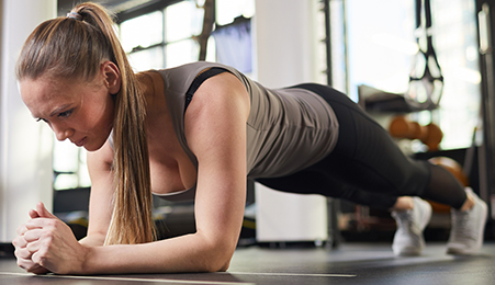 strong young woman working on her core muscles planking on the ground. Supporting her body on her forearms and the tip of her toes