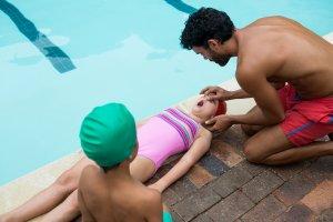 Lifeguard assisting unconscious girl near swimming pool